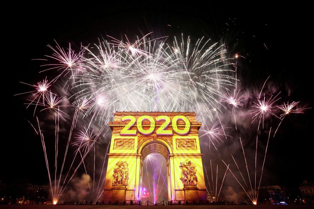 Новогодний фейерверк освещает небо над Триумфальной аркой во время празднования на Елисейских полях в Париже. Франция, 1 января 2020 года