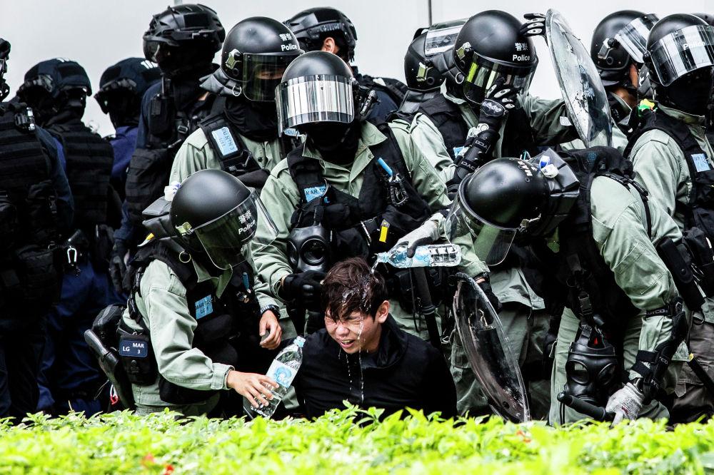 Полиция помогает мужчине который  получил в лицо газ от перцового баллончика во время демонстрации в Гонконге. 5 января 2020 года