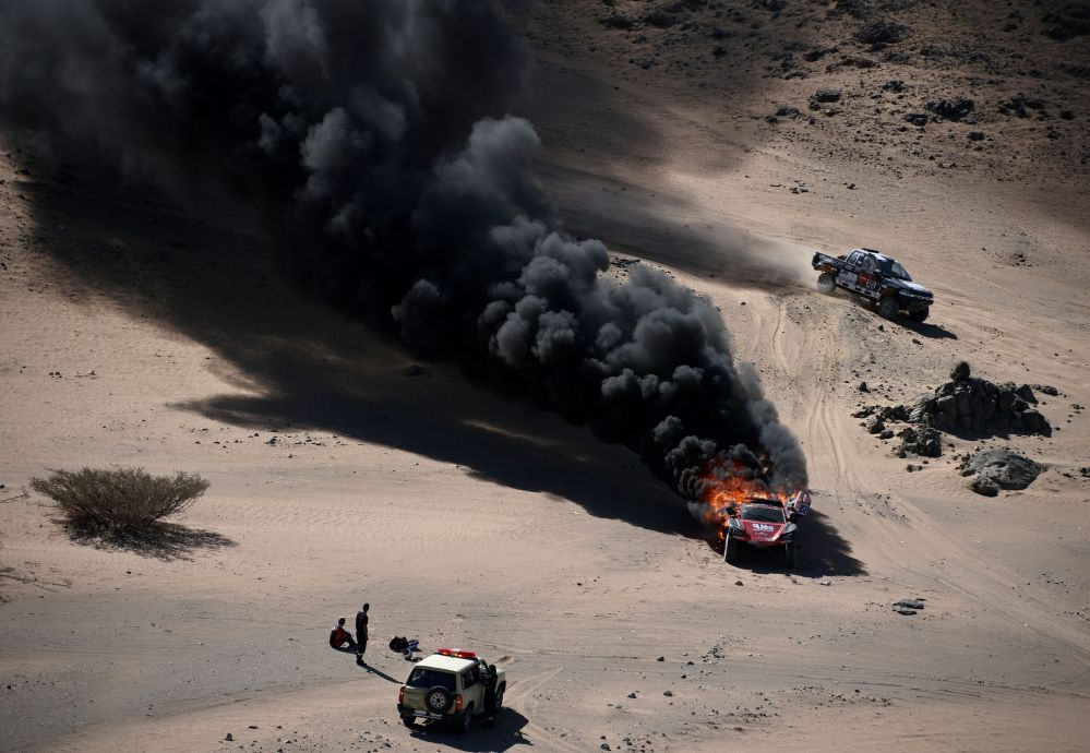 Французский водитель Ромен Дюма и второй водитель Александра Винок наблюдает за горящей машиной во время 1-го этапа Дакара 2020 между Джиддой и Аль-Ваджхом. Саудовская Аравия, 5 января 2020 года