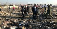 Члены спасательной команды вместе с людьми проверяют обломки самолета, принадлежащего Международным авиалиниям Украины, после взлета из иранского аэропорта Имама Хомейни на окраине Тегерана. Иран, 8 января 2020 года