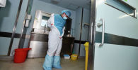 Медицинский работник снимает защитный костюм. Архивное фото