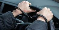Мужчина в наручниках за рулем. Иллюстративное фото