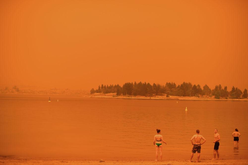 Люди у озера Джиндабайн в австралийском штате Новый Южный Уэльс, небо над которым окрашен оранжевым цветом из-за бушующих по стране лесных пожаров