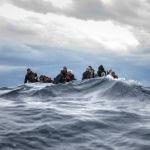 Беженцы из Марокко и Бангладеш сидят в переполненной деревянной лодке в Средиземном море, ожидая помощи испанских спасательных служб