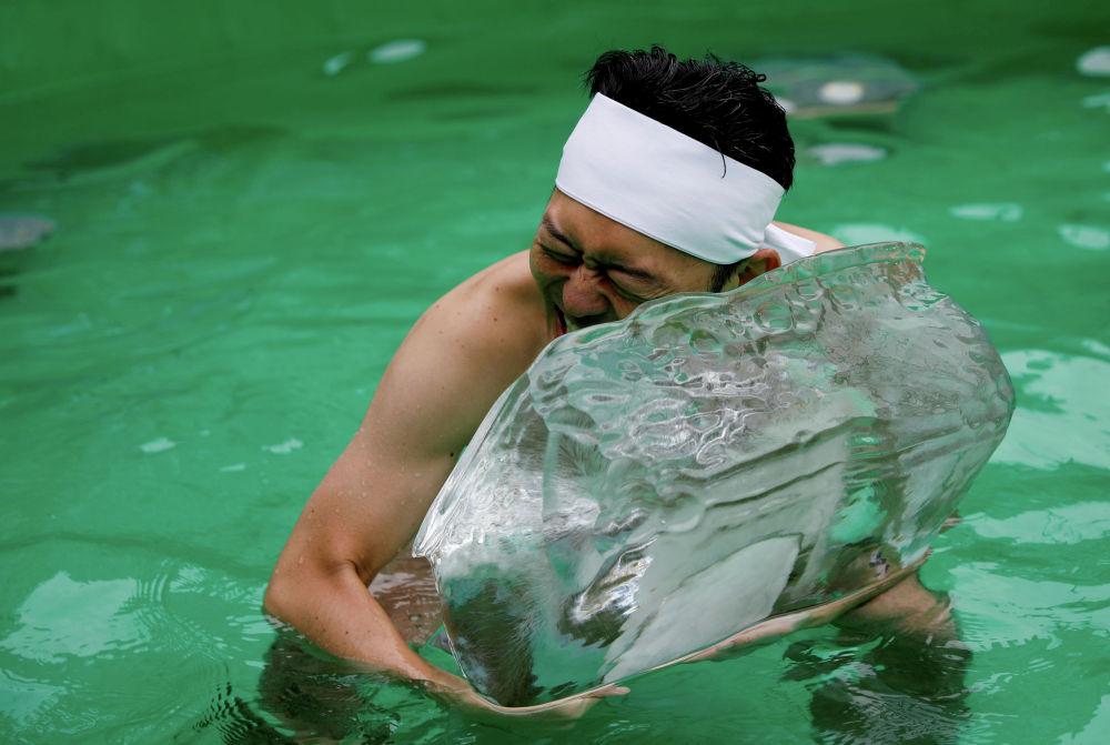 Мужчина купается на ледяной воде во время традиционного фестиваля очищения души в храме Теппозу Инари в Токио (Япония)