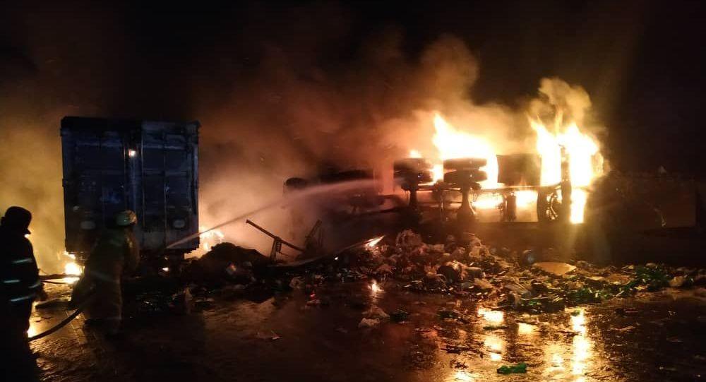 Сотрудники МЧС на месте ДТП с двумя грузовиками на Иссык-Куле после столкновения, которого погибли два человека