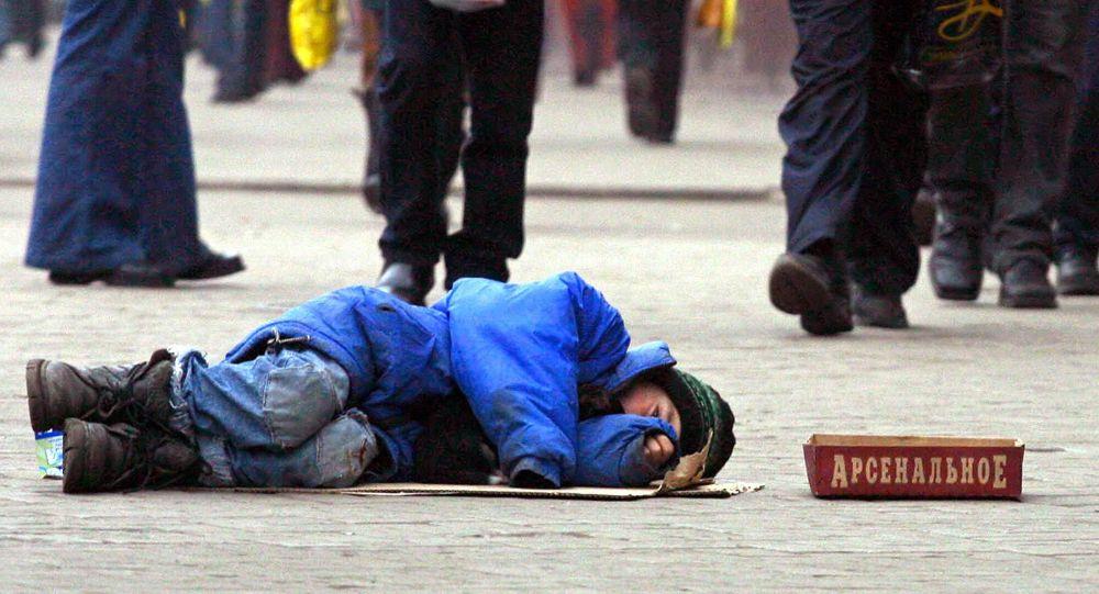 Мальчик лежит на земле и просит милостыню. Архивное фото