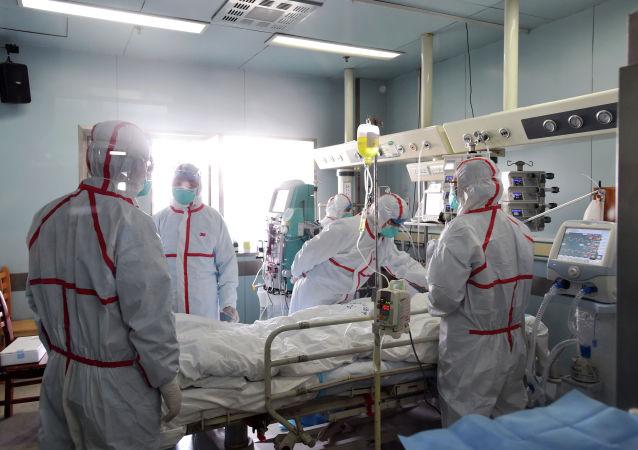 Медицинские работники осматривают пациента больного неизвестным вирусом. Архивное фото