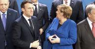 Президент Франции Эммануэль Макрон и канцлер Германии Ангела Меркель растерялись из-за того, что глава России Владимир Путин задержался перед церемонией фотографирования.