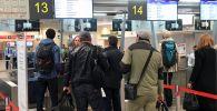 Пассажиры у стойки регистрации в аэропорту. Архивное фото