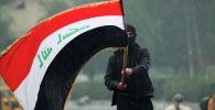 Иракский демонстрант с иракским флагом в ходе продолжающихся антиправительственных протестов в Багдаде.