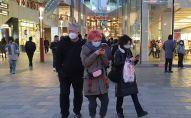 Прохожие в защитных масках на одной из улиц в Пекине.Архивное фото
