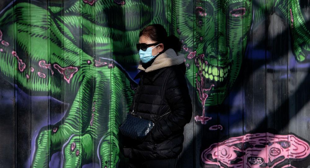 Женщина в защитной маске идет по улице в Пекине 23 января 2020 года.
