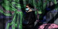 Пекинде маска кийип жүргөн аял. Архивдик сүрөт