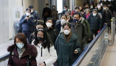 Пассажиры в медицинских масках прибывающие в аэропорт.