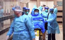 Медицинский персонал переводит пациента с подозрением на случай нового коронавируса в больнице королевы Елизаветы в Гонконге. Китай, 22 января 2020 года