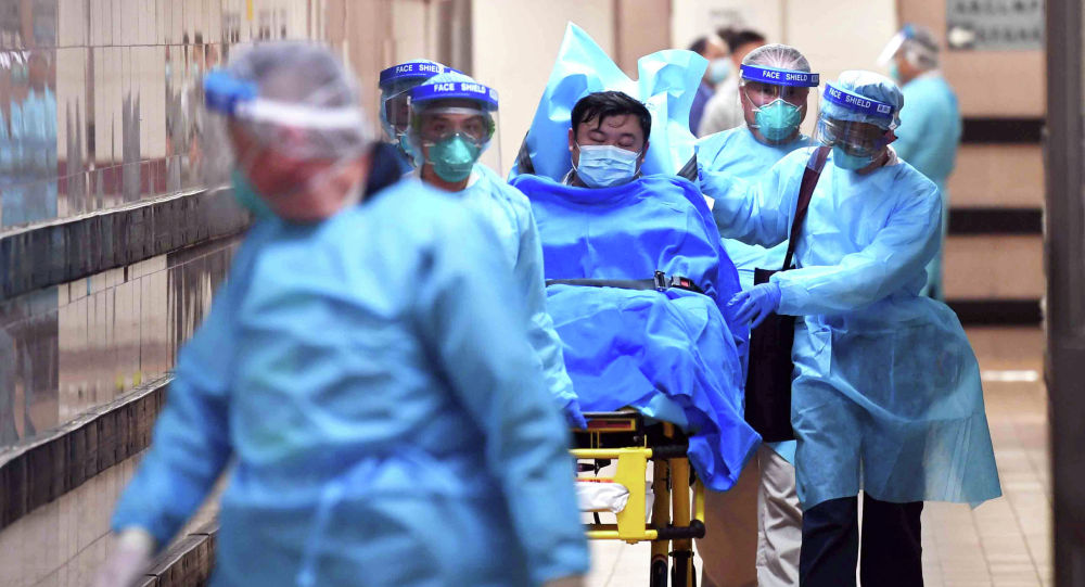 Медициналык персонал жаңы коронавирусу болушу мүмкүндүгү шеги бар пациентин ооруканада алып кетүүдө. Гонконг шаары