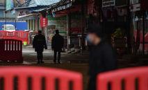Охранники патрулируют возле оптового рынка морепродуктов Хуананя, где 24 января 2020 года в Ухане был обнаружен коронавирус.