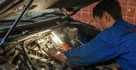 Мастер во время установки газобаллонного оборудования на авто в Бишкеке