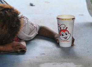 Мальчик просит милостыню у прохожих на эстакаде в Маниле. 20 января 2011 года