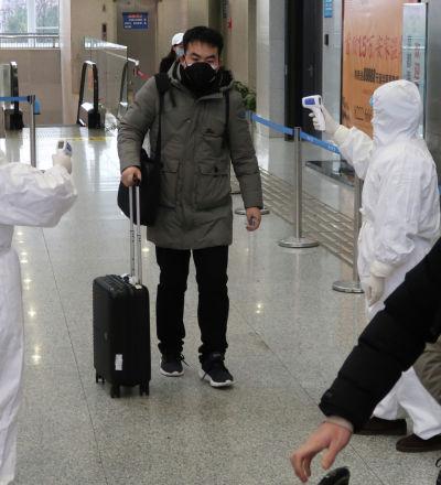 Рабочие в защитных костюмах проверяют температуру пассажира, прибывающего в город Сяньнин, граничащим с Уханом, Китай. 24 января 2020 года