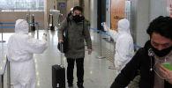 Ухань шаарынын жашоочусун текшерип жаткан медициналык кызматкерлер