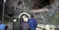 Люди стоят возле разрушенного здания после землетрясения в Элязыге. Турция, 24 января 2020 года