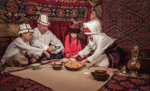 Семья в национальной одежде кыргызов сидят за дасторконом в юрте (жилища кочевников) на джайлоо Кок-Жайык.