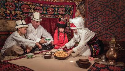 Семья в национальной одежде кыргызов сидят за дасторконом в юрте. Архивное фото