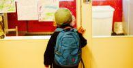 Ученик младших классов смотрит на рисунки в школе. Иллюстративное фото
