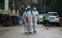 Работники местного отдела по контролю и профилактике заболеваний в защитных костюмах дезинфицируют жилой район после вспышки нового коронавируса в Руичане, провинция Цзянси, Китай, 25 января 2020 года