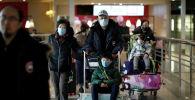 Туристы из рейса Air China из Пекина надевают защитные маски по прибытии в аэропорт имени Шарля де Голля в Париже, Франция, 26 января 2020 года