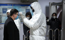 Медицинский работник в защитном костюме измеряет температуру пассажира у входа на станцию метро в Пекине. 26 января 2020 года