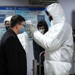 Медицинский работник в защитном костюме измеряет температуру пассажира у входа на станцию метро в Пекине. 26 января 2020 года.