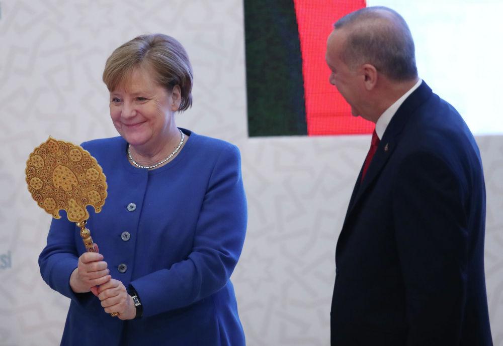 Канцлер Германии Ангела Меркель улыбается, когда она получает зеркало в подарок от президента Турции Реджепа Тайипа Эрдогана 24 января 2020 года