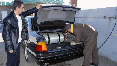 Рабочий заправляет бензобак автомобиля на автозаправочной станции. Архивное фото