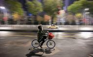 Человек, одетый в защитную маску, едет на велосипеде по улице в Ухане, городе в эпицентре вирусной эпидемии, в результате которой погибли по меньшей мере 56 человек и заразились почти 2000 человек. 26 января 2020 года