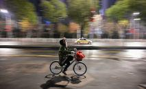 Ухань шаарында велосипедчен бараткан кыз. Архивдик сүрөт