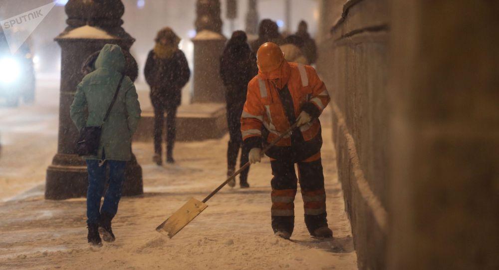 Сотрудник коммунальных служб убирает снег на одной из улиц Москвы. Архивное фото