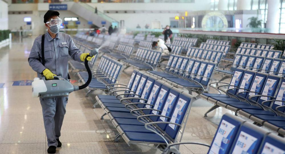 Рабочие в защитной маске дезинфицируют зал ожидания после вспышки нового коронавируса на железнодорожной станции Нанкин в провинции Цзянсу. Китай