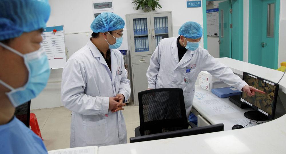 Врачи смотрят на экран, на котором показано отделение, где лежат пациенты инфицированные коронавирусом, Ухань, Китай. 28 января 2020 года