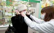 Сотрудница одной из аптек консультирует покупательницу о правилах пользования медицинской маской. Архивное фото