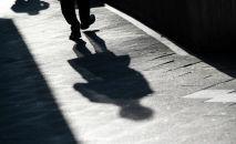 Мужчина отбрасывает длинную тень на тротуар. Архивное фото