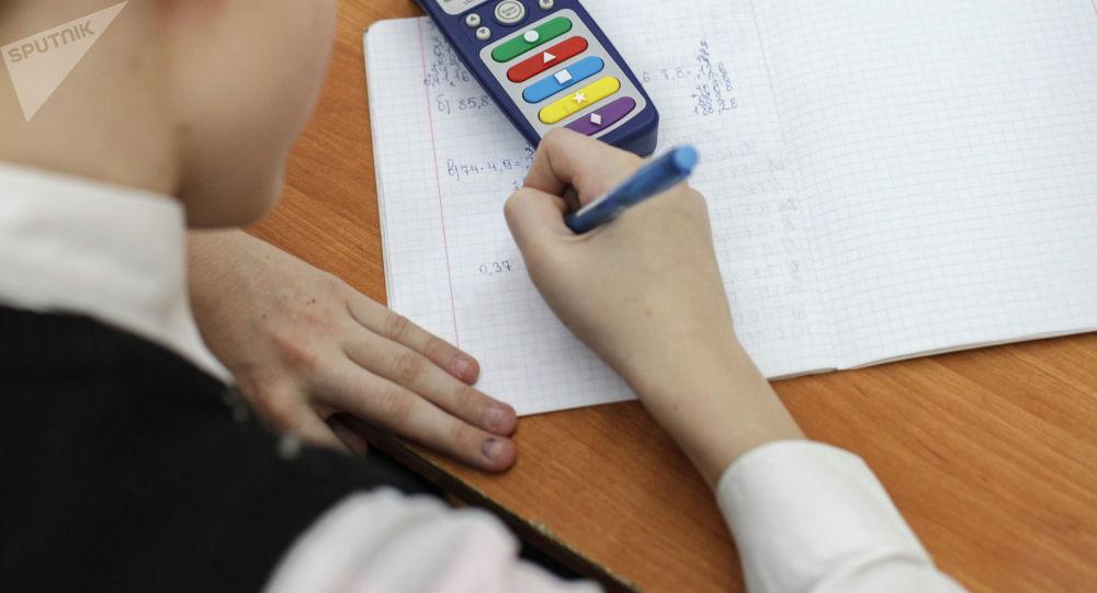Ребенок пишет в тетради во время занятий. Архивное фото