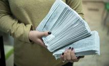 Женщина держит пачку медицинских масок в Бишкеке