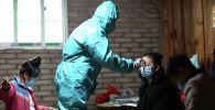 Медицинский работник в защитном костюме проверяет температуру девушки. Архивное фото