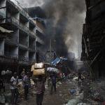 Эл Лагос шаарында жайгашкан Балогун базарында өрттөн калган товарларды ташууда