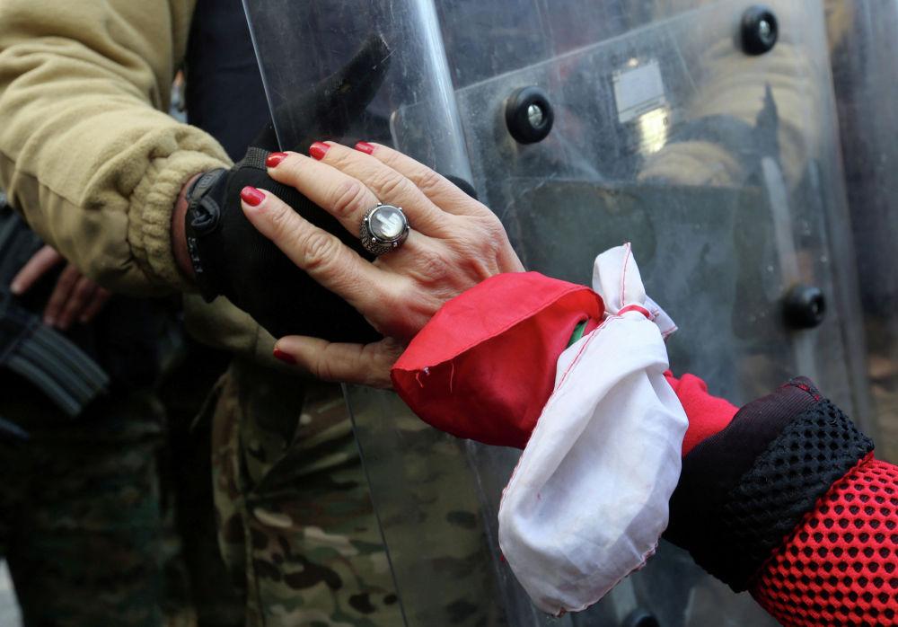 Ливандын Бейрут шаарында саясий элитага каршы нааразычылыкка чыккан аял аскер жоокеринин колун кармап жатат