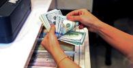 Сотрудник обменного пункта считает банкноты в долларах США. Архивное фото