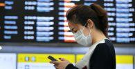 Девушка в медицинской маске в аэропорту